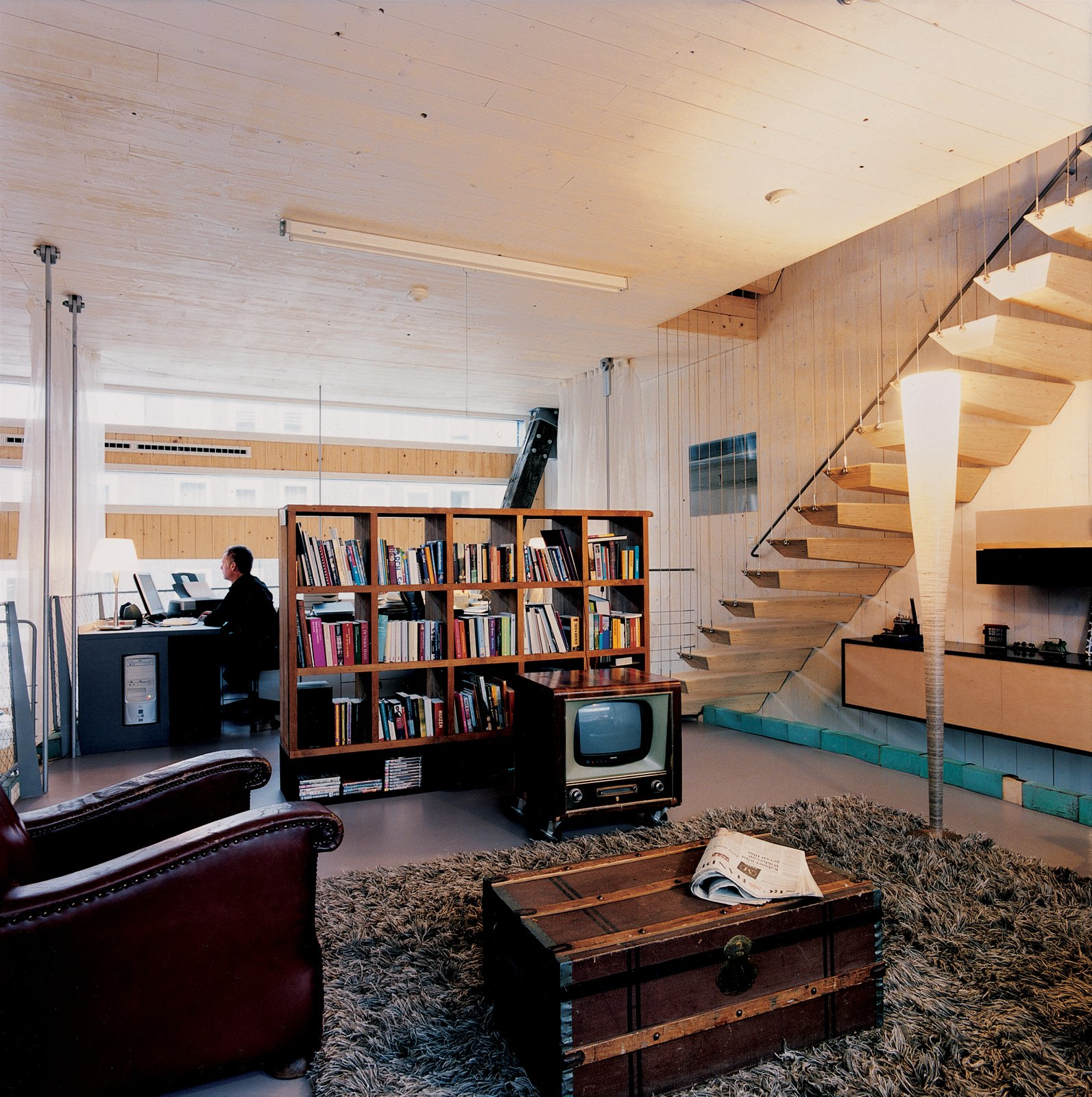 Weijnen's office adjoins the living room, an open area furnished with a 1950s television cabinet (housing a new TV), a battered armchair found on the street, a Fellice Rosso leather sofa, and a Koot Licht floor lamp.  Photo 3 of 10 in A Suspended Living Room Floats Like an Air Ship
