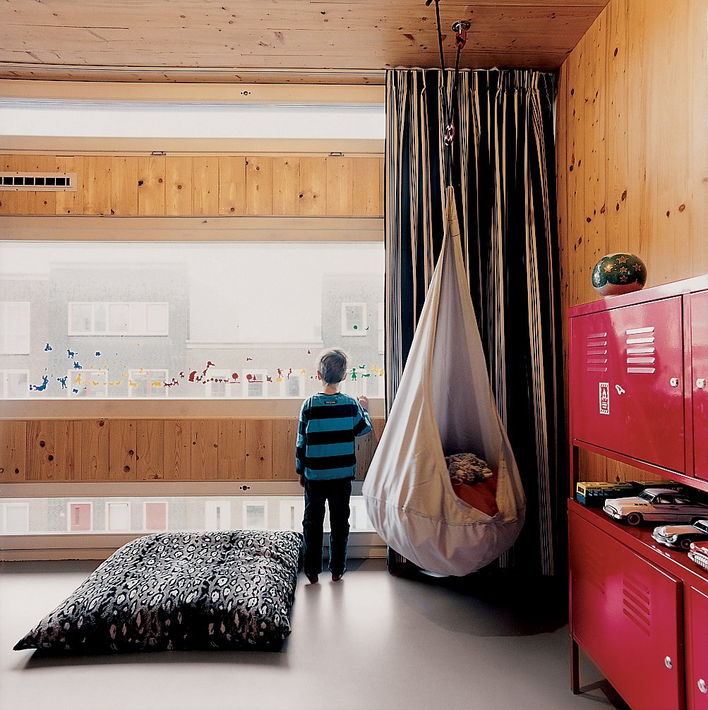 Finn's street-facing room at the front of the house is enlivened by varying window sizes. Tagged: Kids Room, Bedroom, Pre-Teen Age, Boy Gender, Shelves, and Storage.  Photo 4 of 10 in A Suspended Living Room Floats Like an Air Ship