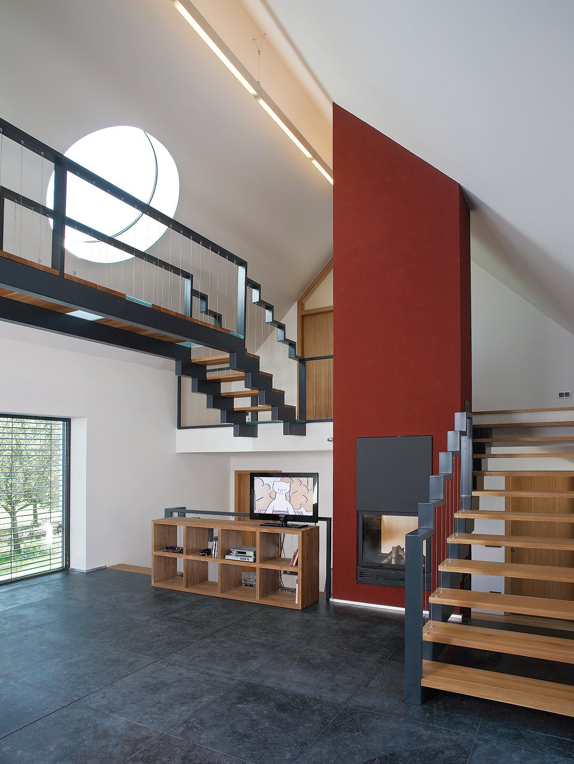 "Circular ""sun disks"" cut into the slanted roof create light shafts that move throughout the day, casting angular shadows as they pass over the steel staircases and catwalk. Tagged: Staircase, Metal Railing, and Wood Tread.  Photo 2 of 4 in A Striking Bohemian Geothermal Home"