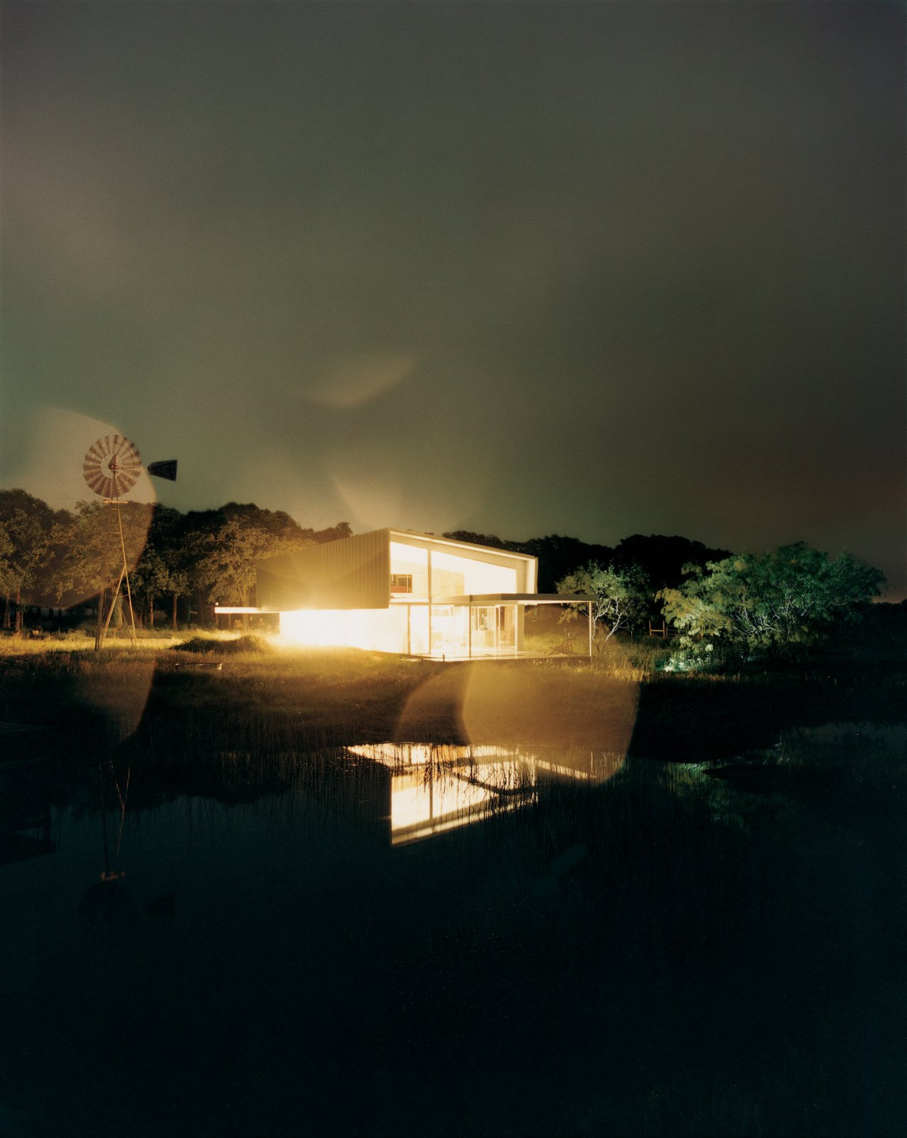 At night, the entire studio glows like a lantern, its light amplified by the reflection in the seasonal pond. I Tagged: Exterior, House, and Farmhouse Building Type.  Photo 5 of 13 in Lone Star