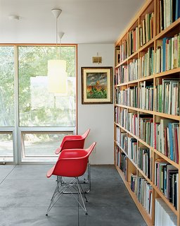 Up above the sitting room a duo of Eames shell chairs and a bank of luminous operable windows await a pair of weary readers.
