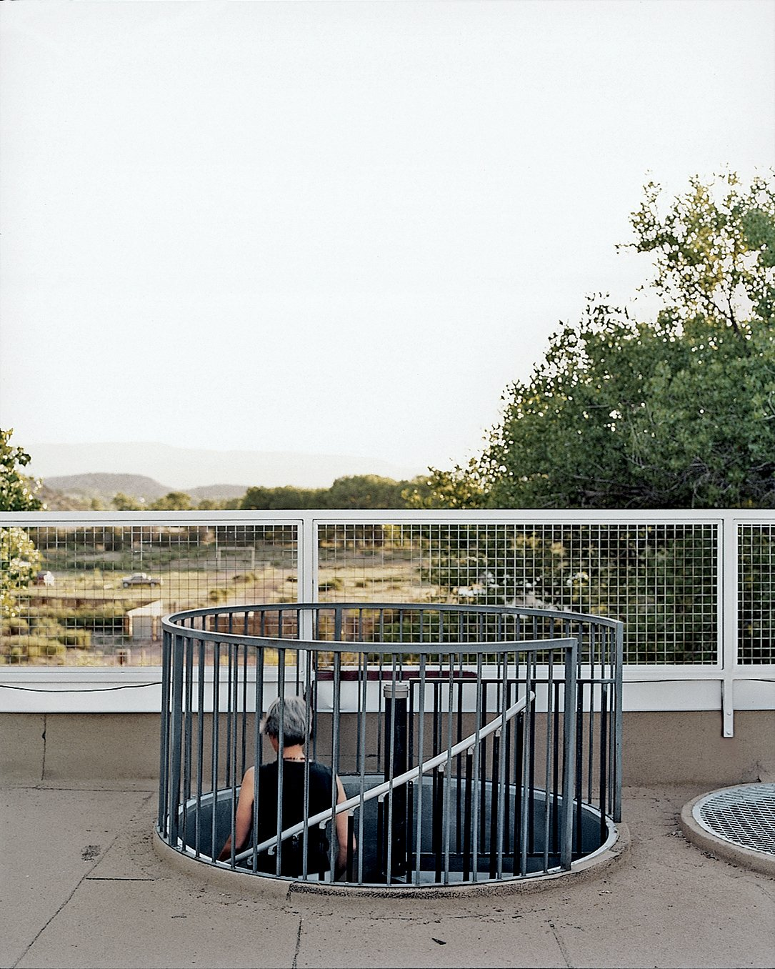 """Brigitte descends one of two locally fabricated steel cylinders: her """"stairway to the stars."""" Tagged: Staircase, Metal Tread, and Metal Railing.  Photo 6 of 10 in Abiquiu Debut"""