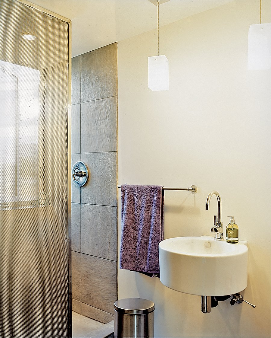 A perforated metal screen serves as a shower curtain. Tagged: Bath Room, Wall Mount Sink, Enclosed Shower, Pendant Lighting, and Stone Tile Wall.  Photo 9 of 10 in Abiquiu Debut