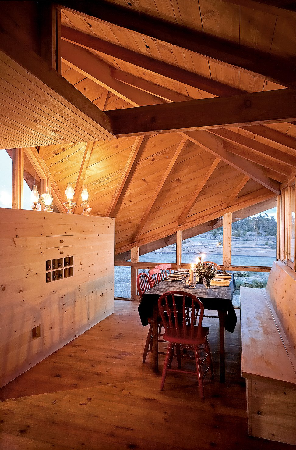 Angled openings in the roofline function as both windows and vents, allowing views and cross-breezes. A dining table completes the nearly all-wood room.