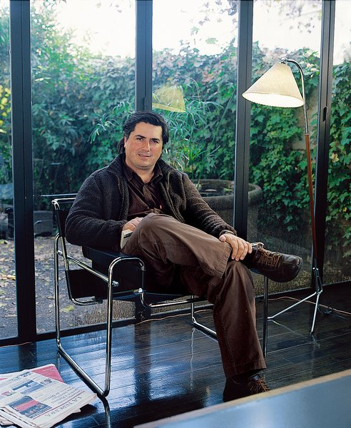 Architect Sebastián Irarrázaval relaxes in a Marcel Breuer–designed Wassily Chair in his 50-year-old house that he has renovated to include walls of windows and flexible, open interior spaces.