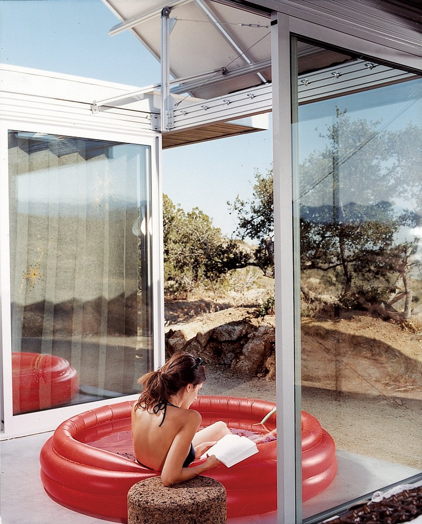 """The living space and bedrooms are separated by two small courtyards. Linda Taalman reclines in a small, inflatable wading pool in the home's """"firecourt,"""" facing south toward the desert. Tagged: Outdoor, Small Pools, Tubs, Shower, and Desert.  Photo 4 of 9 in iT House, Joshua Tree"""