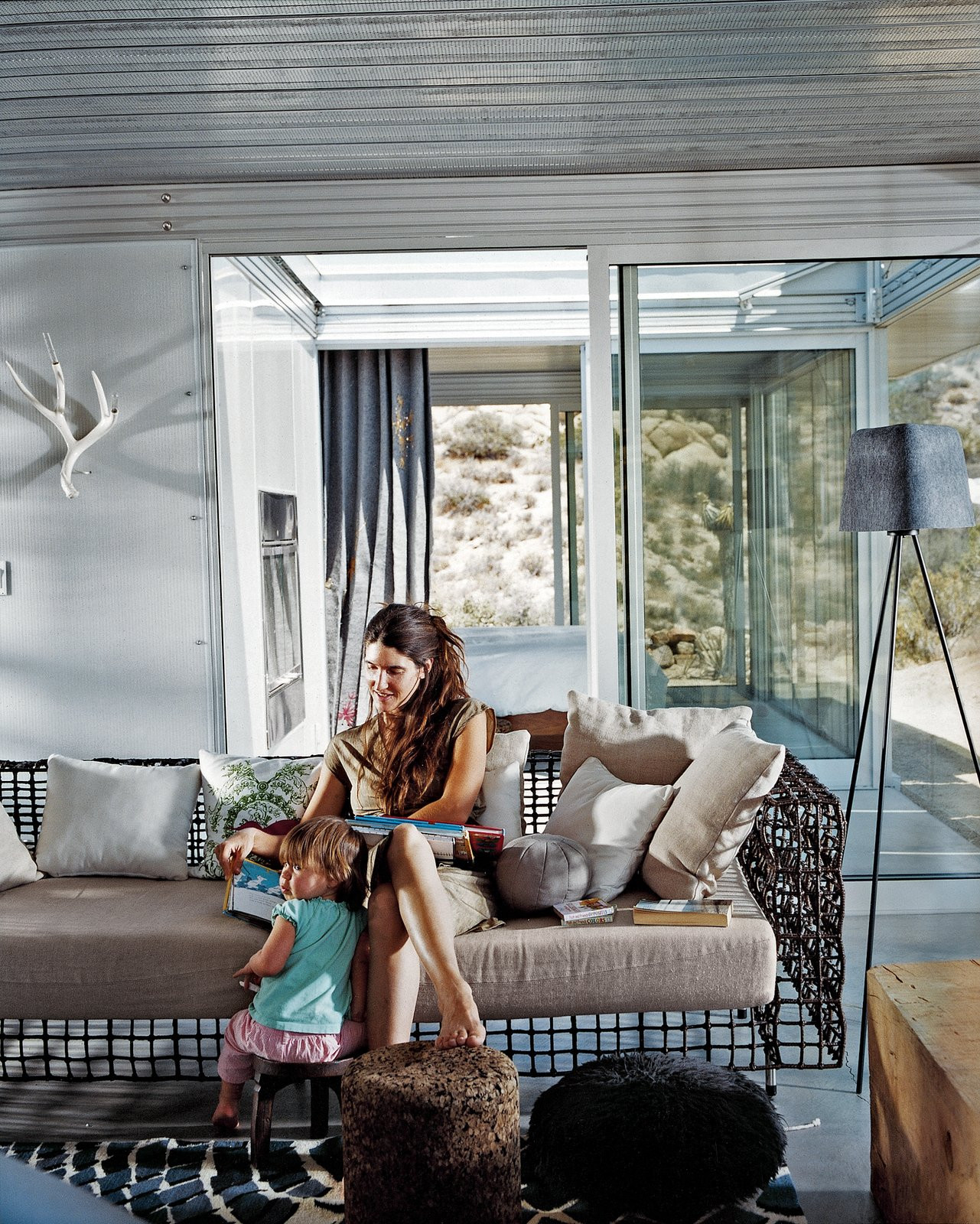 Taalman sits with their daughter, Oleana, in the living room on a metal lounge designed by Kenneth Cobonpue. Glass walls emphasize views and greatly expand the sense of space in the 1,100-square-foot house. Through the glass wall behind her is the fire court and behind that the master bedroom. iT House, Joshua Tree - Photo 7 of 9