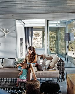 Taalman sits with their daughter, Oleana, in the living room on a metal lounge designed by Kenneth Cobonpue. Glass walls emphasize views and greatly expand the sense of space in the 1,100-square-foot house. Through the glass wall behind her is the fire court and behind that the master bedroom.