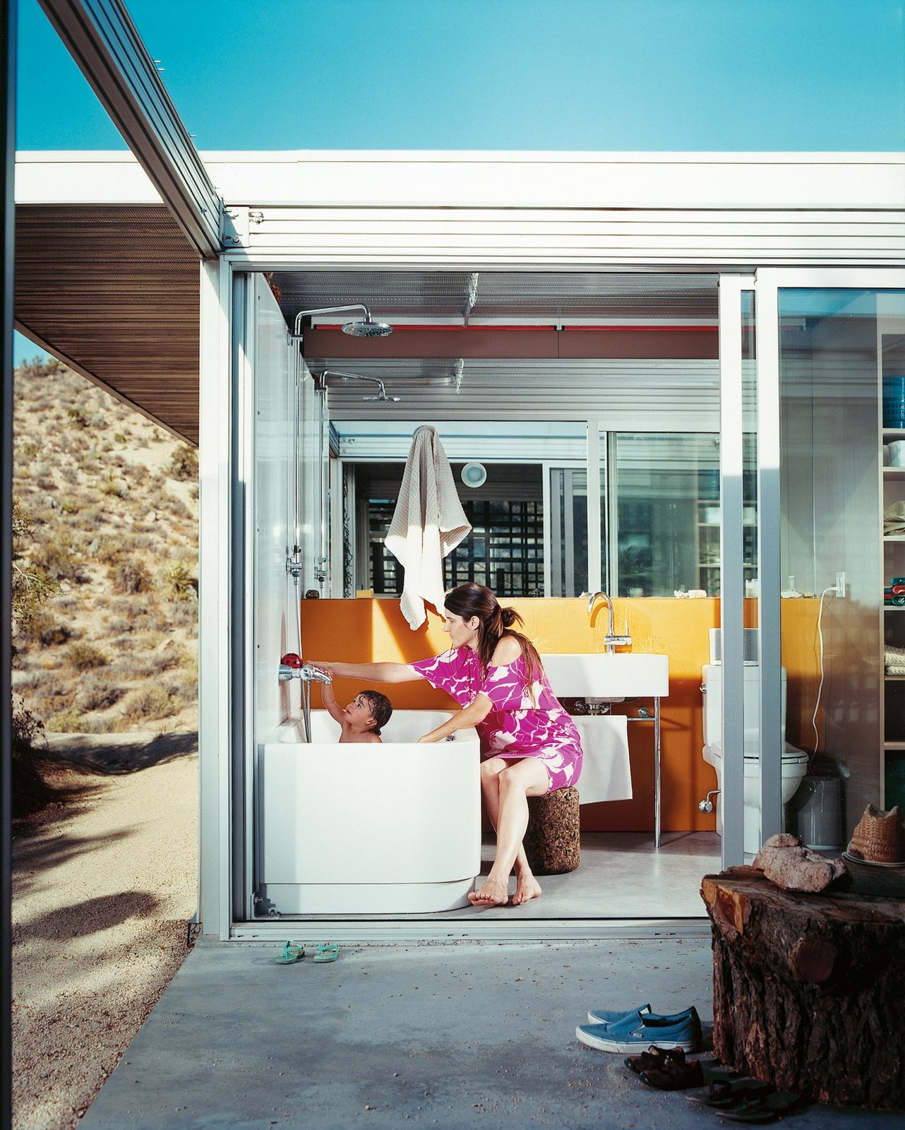 Taalman bathes Oleana, with doors opened wide onto the courtyard. The bath and basin are by Duravit, the orange wall by Three Form.  Photo 8 of 9 in iT House, Joshua Tree