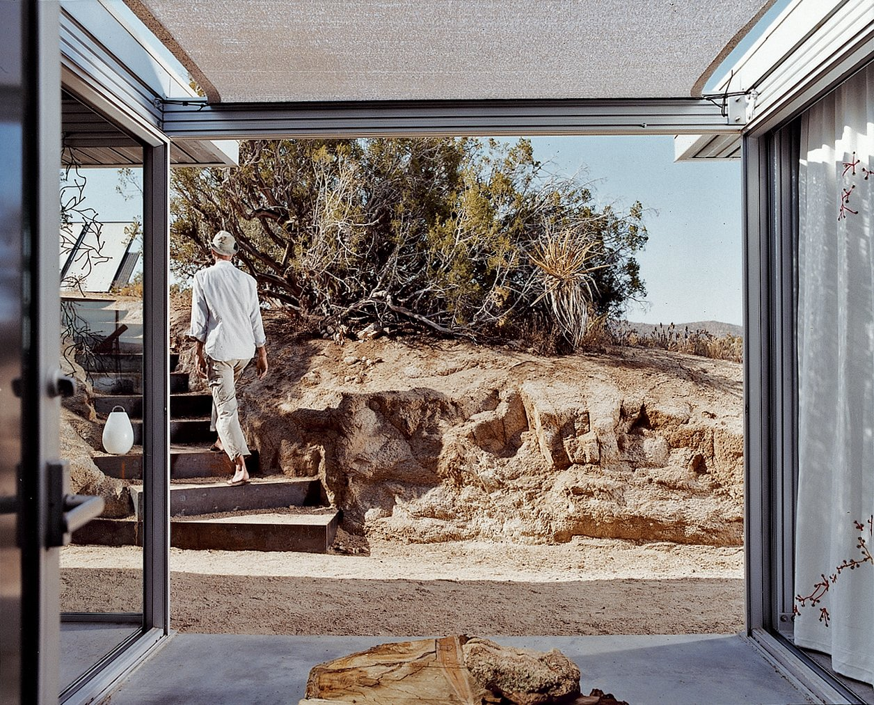 A view out from the entrance lobby shows Koch leaving the house. He made the stairs' steel risers himself, with the help of his cousin, Chris Wilson. Tagged: Outdoor, Small Patio, Porch, Deck, and Concrete Patio, Porch, Deck.  Photo 9 of 9 in iT House, Joshua Tree