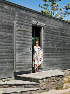 Emma Worple dries off from a swim at the cedar-clad sleeping cabin; the door slides shut to shield the cabin from harsh winter winds.