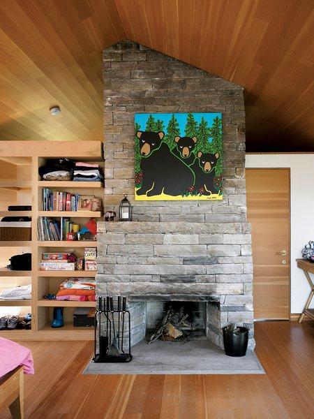 Inside the sleeping cabin, a fireplace built of local granite marks the midpoint between two bedrooms and a bathroom.