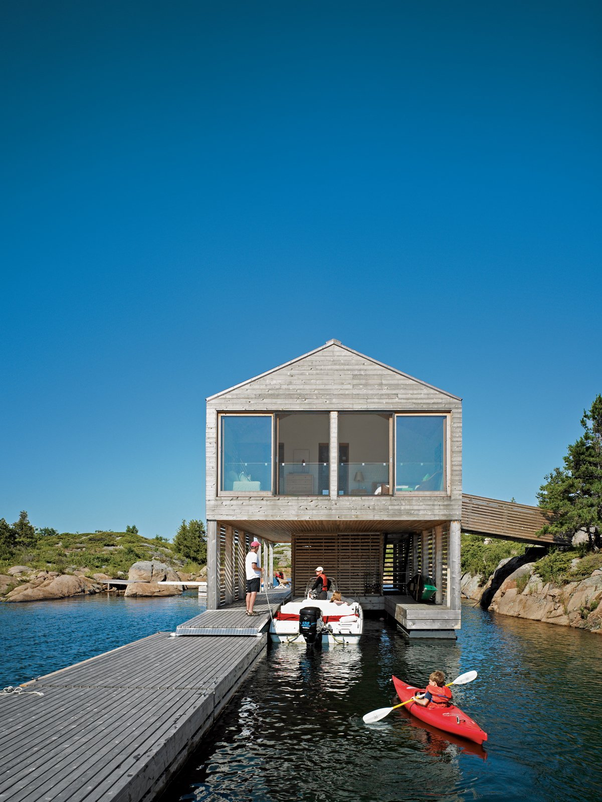 All of the Worples' guests arrive by boat to the lower level of the Floating House. Tagged: Outdoor, Wood Patio, Porch, Deck, and Decking Patio, Porch, Deck.  Photo 6 of 16 in Floating House, Lake Huron
