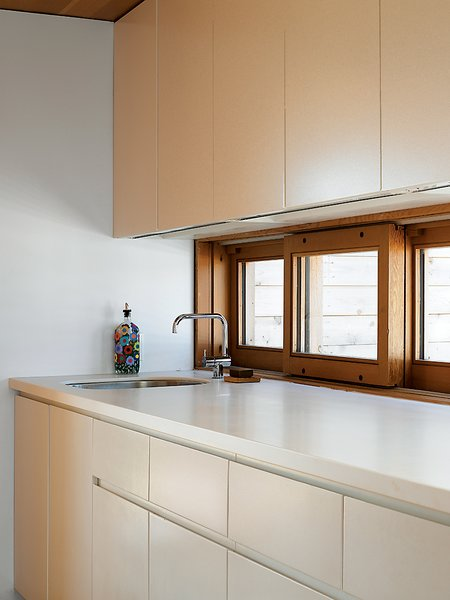 """Upstairs in the Floating House, building codes didn't allow a full kitchen, but a galley kitchenette continues the compound's simple palette of white and Douglas fir. """"I love how understated it is,"""" says Worple."""