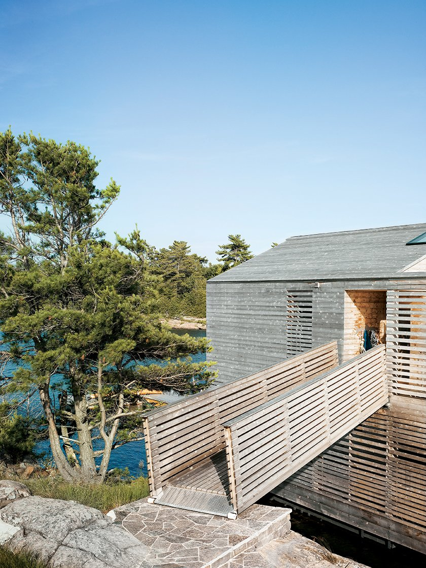 A footbridge connects the Floating House to the island. Tagged: Exterior, Wood Siding Material, and House.  Cabins & Hideouts by Stephen Blake from Floating House, Lake Huron