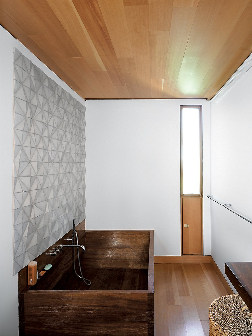 In the bathroom, a custom ceramic backsplash designed by Meredith and Sample joins an iroko-wood tub created by their students a the University of Toronto. Tagged: Bath Room, Soaking Tub, Freestanding Tub, and Medium Hardwood Floor.  Photo 10 of 16 in Floating House, Lake Huron