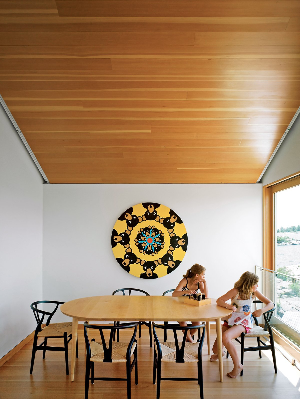 Emma Worple and a friend enjoy an open view of the island from the dining area. Tagged: Dining Room, Table, Medium Hardwood Floor, and Chair.  Photo 13 of 16 in Floating House, Lake Huron