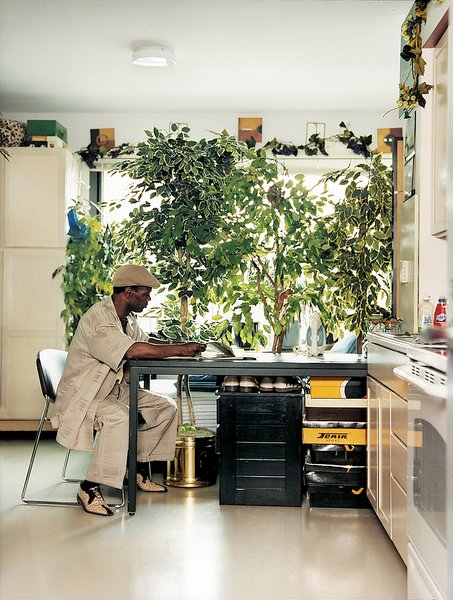 Ernest Gladney reads alone at a worktable in his bedroom. Tall houseplants give Gladney a shade of privacy against the passing cars on Clybourn Avenue.