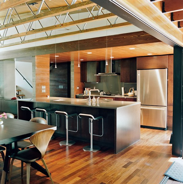 The couple opted for a smaller kitchen without fussy appliances and a larger dining area. They concentrated on achieving a high-quality space through carefully chosen furnishings, including the Cross Extension table in wenge a Cherner side chair, and the LEM piston stools, all from Design Within Reach.