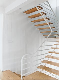 The main staircase consists of simple oak treads that cantilever out from side walls sheathed in natural vertical board and are supported on the other side by a continuous grill-like railing truss.