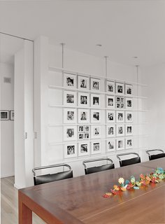 Bauhaus by the Sea - Photo 6 of 8 - In the dining room, Mies van der Rohe chairs surround a custom-made cherry table. Black-and-white photographs of Sasseen's children and grandchildren are arranged systematically on the back wall.
