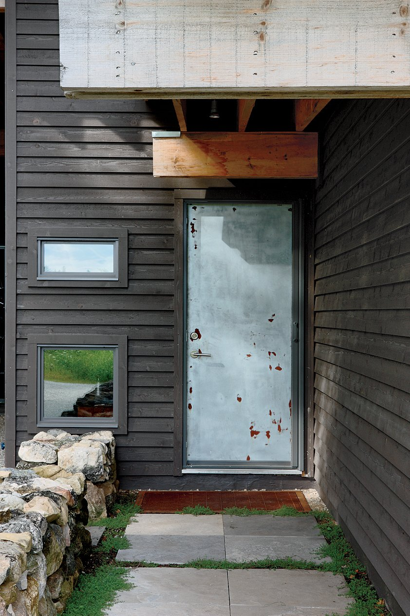 An unpainted door, in line with Sherbanuk's stripped-down aesthetic, marks the front entrance. Scrap House - Photo 6 of 8
