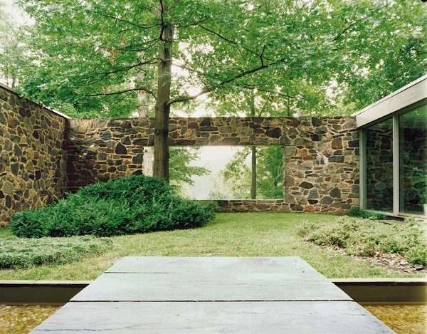 A large rectangular cut in the back wall of the house creates views from the entrance through a courtyard to the trees and lake beyond.