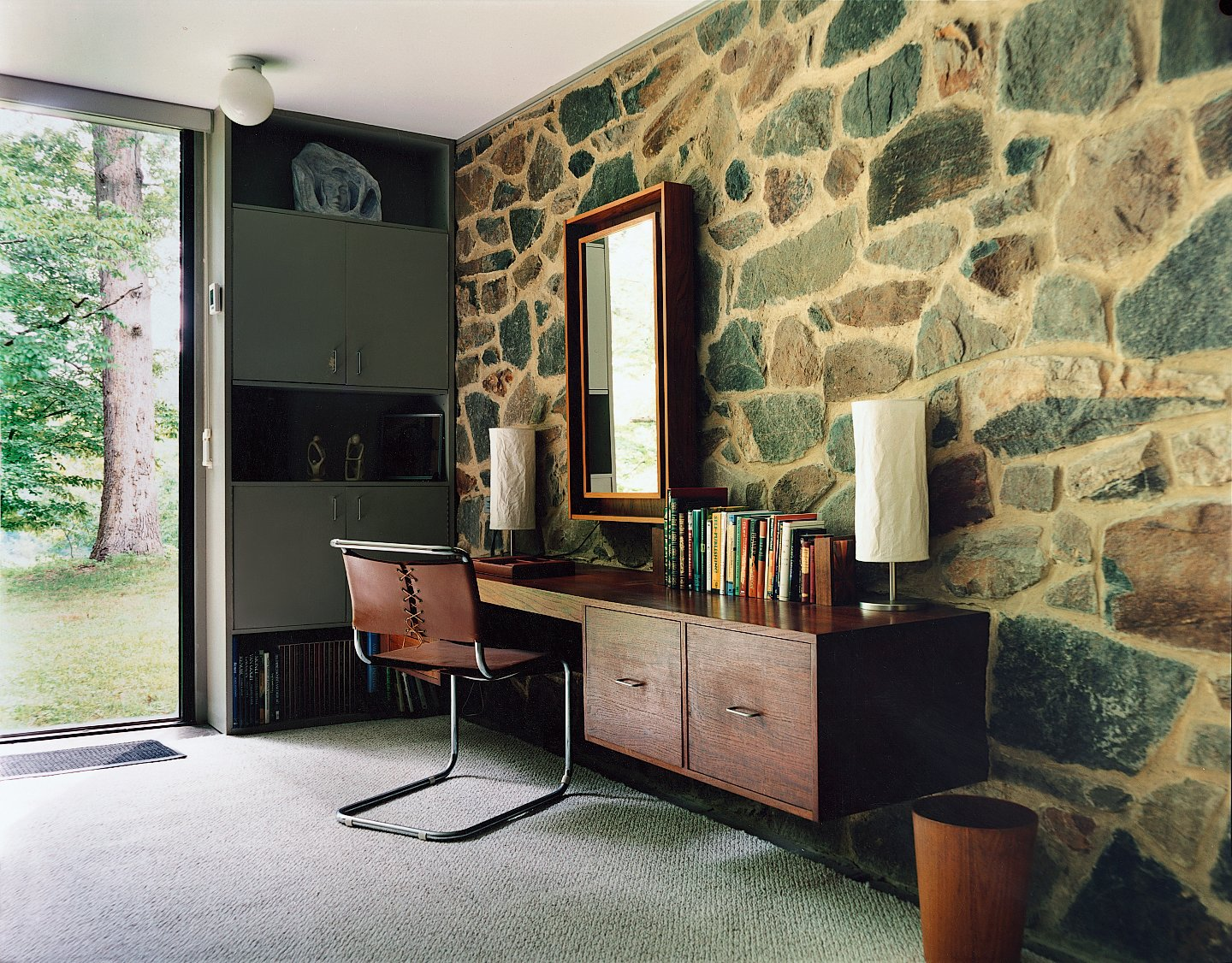 Although the house was refurbished before North bought it in 1996, it still includes some of Breuer's original built-in furniture, including the desk in the bedroom, as well as a chair designed by the architect. Tagged: Office, Desk, Chair, Lamps, and Rug Floor.  Photo 5 of 9 in Marcel Breuer Hooper House II