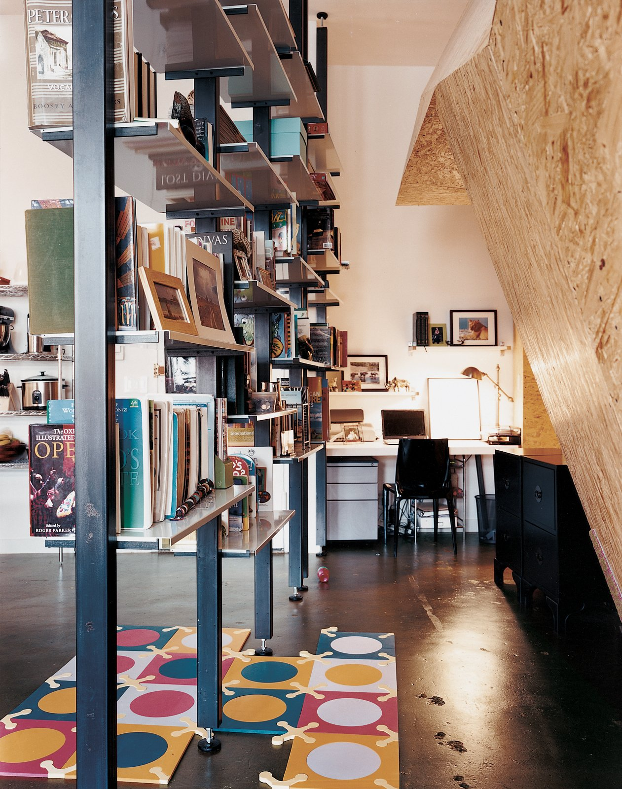 Custom-fabricated modular bookshelves create a corridor leading to the home office.  Storage by Dwell from Hive Minded