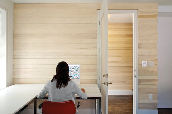 The ground floor office, where irregularly white-ash wood panels, sourced from Massachusetts Woodlands Cooperative, line the walls.