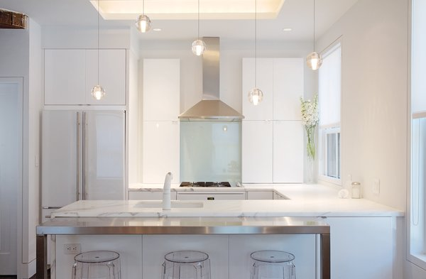 After removing two small kitchens from the original building, the home's new kitchen dominates the second floor, opening onto the living area. Fixtures in the kitchen include 14 Series pendants by Omer Arbel for Bocci, and Charles Ghost stools by Philippe Starck for Kartell.