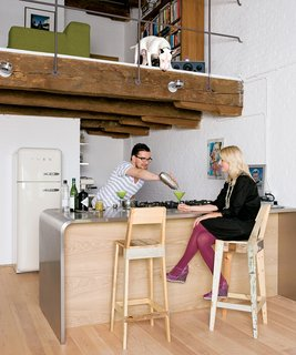 Until Hindman and Carr moved in, the space had never been a home. Carr cooks every day, so the compact kitchen was a natural starting point for the renovation. It features an industrial curving steel counter, which also functions as a breakfast bar. The Scrap stools are by contemporary Dutch designer Piet Hein Eek.