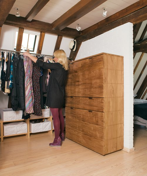 Few structural additions were made to the apartment, but the half wall in the top-floor bedroom was one of them The wall and an elegant chest of drawers by Peter Laszlo create storage for clothes without breaking up space. The white-painted brick of the new wall blend in with the original 17th-century walls.