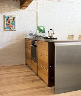 Teak cabinets add warmth to the steel counter in the kitchen, which local designers Op16 created for the couple. The picture was created by the New York graffiti artist Cycle and was purchased at Upper Playground in San Francisco. Exposed electricity cables on the old brick walls enhance the industrial feeling.