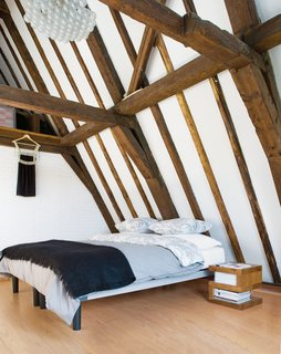 """Vertical Challenge - Photo 9 of 9 - """"Instead of the disappointment we anticipated, there was yet another great space, with an incredible beamed ceiling,"""" says Hindman of seeing the top-floor bedroom for the first time. The wooden frame was left in its natural state. Rody Grauman's 85 Lamps chandelier, a classic from Droog Design, places the 17th-century room squarely in the present."""