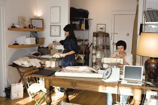 In her sunny studio, Joanna Notkin (left) assembles pillows while Anna Borstand, who manages sampling and production, carefully threads a needle.