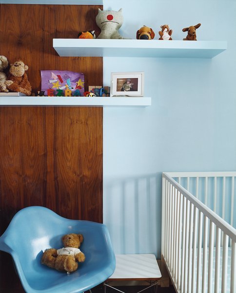Their son's bedroom features skillful use of ordinary birch-finished shelves from Ikea. The 1950s fiberglass shell chair is from Modernica.
