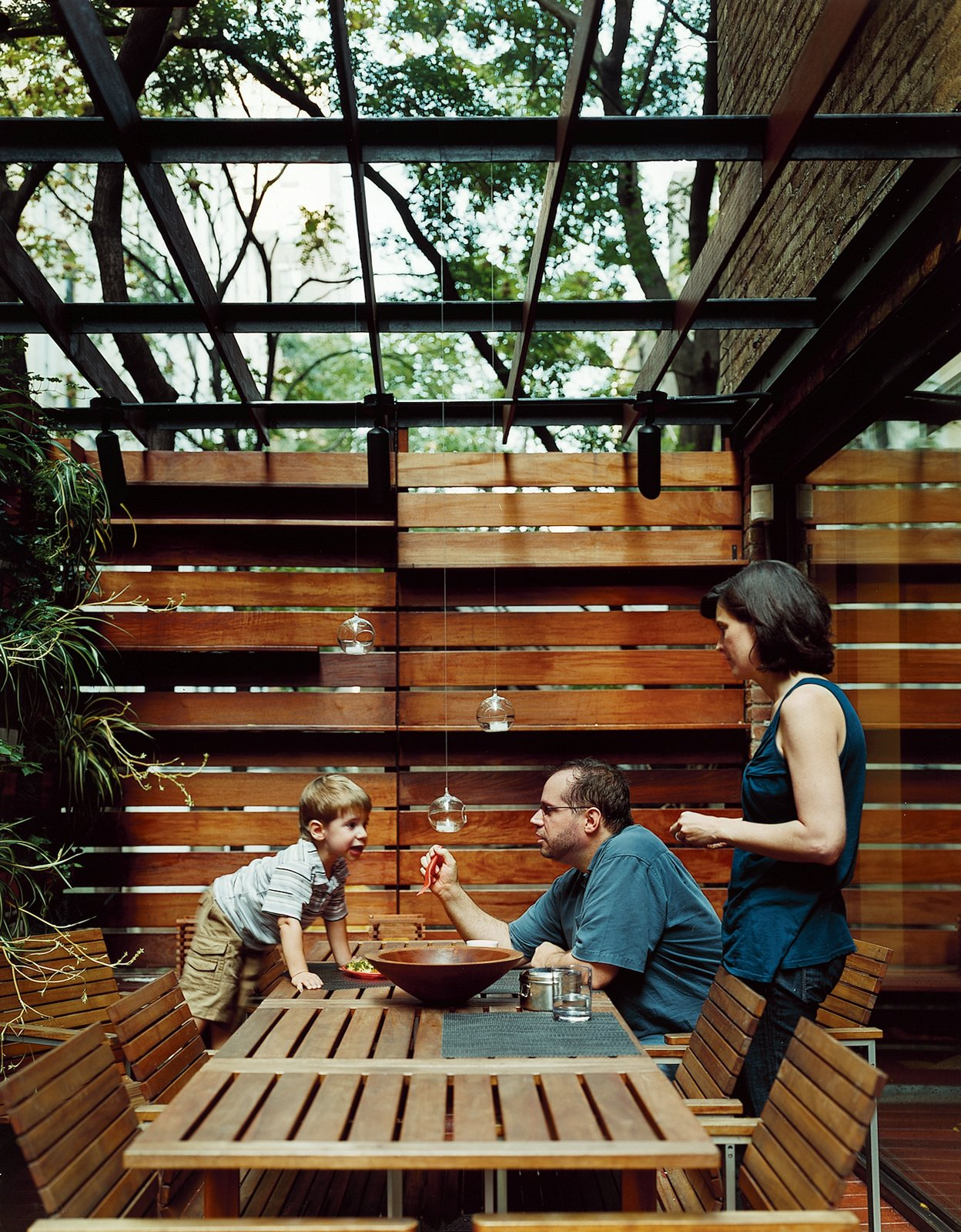 An outdoor dining area is screened for privacy.  Outdoor by Krystal Kincaid from Outdoor Living in NYC