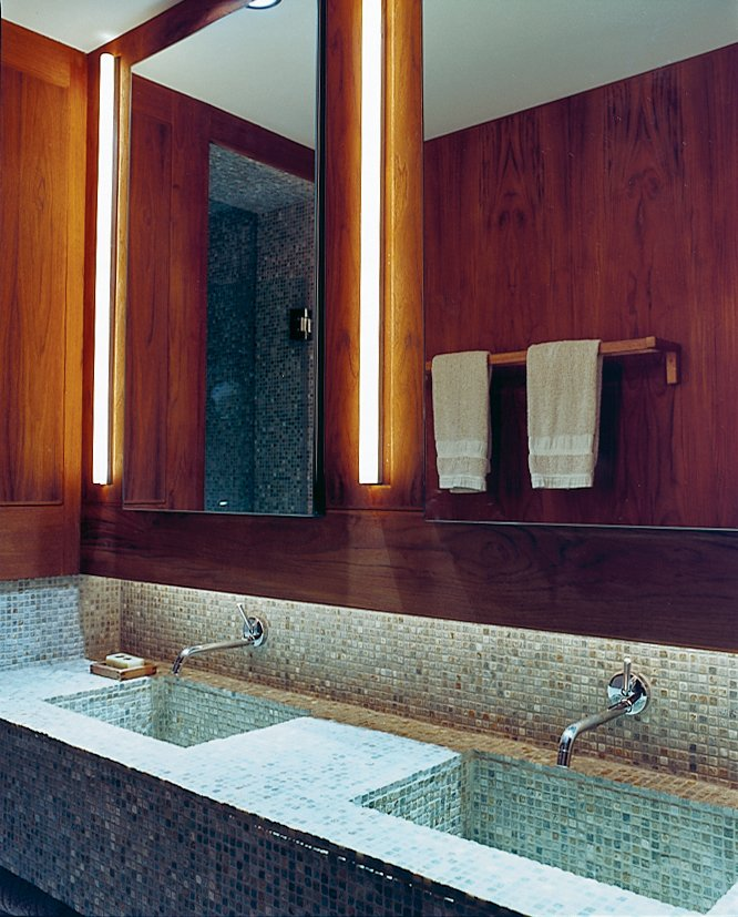 Humble materials are used to good effect throughout the apartment. The bathroom contains ordinary rope lights concealed above the sinks. The tumbled slate mosaic tiles are by Artistic tile. All the wooden bathroom accessories were purchased from Ikea.