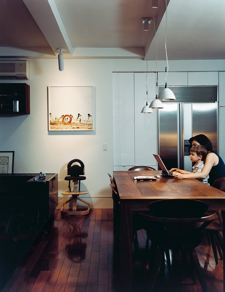 The kitchen has a dining table of black American walnut designed by Brad. The pendant lights are by Ingo Maurer.