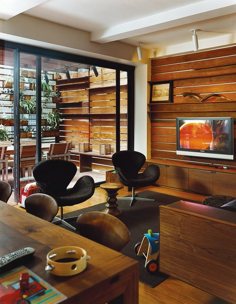 The Zizmors extended their living room by installing an 8-by-15-foot sliding glass door, which leads to an outdoor dining area built six feet above the alley. To make the outdoors feel like it's part of the living room, and not a separate patio, they ran the same horizontal pattern of ipe wood slats from the indoors out.
