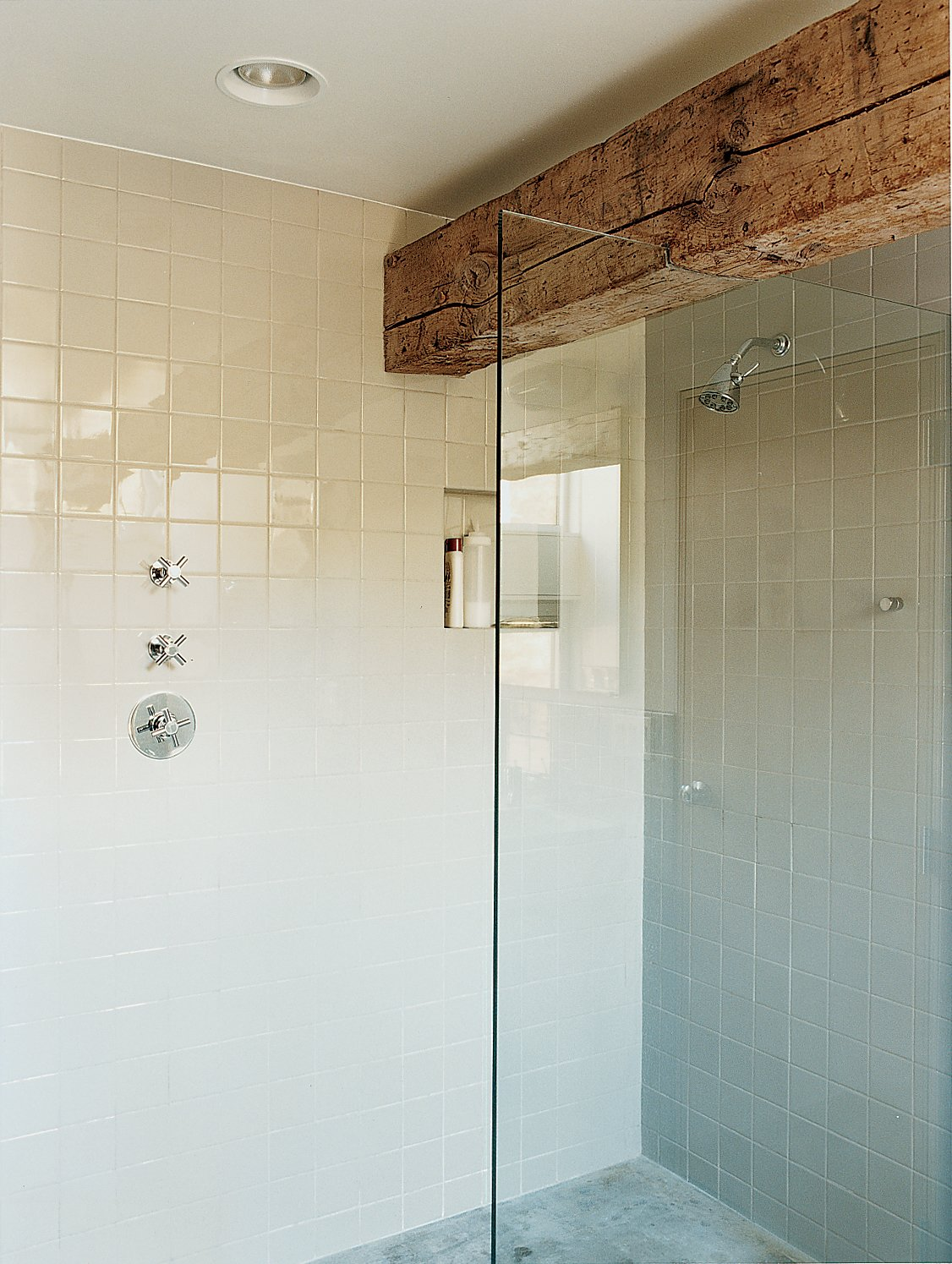 A massive pine beam defines the master bathroom. Tagged: Bath Room, Marble Floor, Subway Tile Wall, Recessed Lighting, and Enclosed Shower.  Photo 6 of 7 in Raising the Barn
