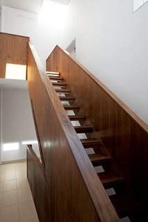 All Clad - Photo 6 of 13 - Despite its dark and boxy exterior, the house's interior is bright, naturally lit, and spacious. Adjaye, a master of the well-placed window, is in top form here. The staircase ascends toward sunlight.