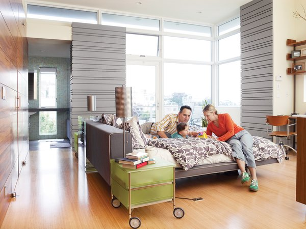 Koshkarian and DiFrancesco lounge on their Poliform bed with their daughter, Zia. The large windows annex an outdoor patio, which extends the already light-filled space into the outdoors.
