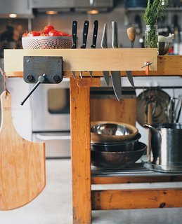 "Summit created a functional kitchen island out of Walz's childhood workbench, fitting <br><br>it with various IKEA parts. The vice makes an ideal wine grabber, and pieces of black iron pipe hold candles. ""Now it's very Martha Stewart,"" jokes Summit."