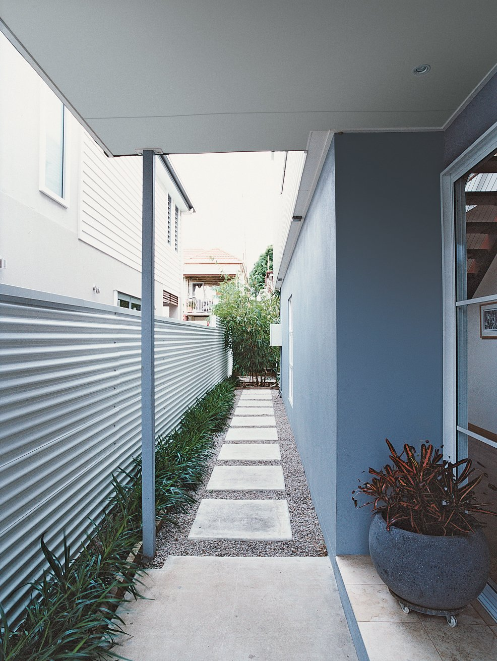 Clayden made the most of his modest lot by building as close to the perimeter as local zoning codes allow. Tagged: Side Yard, Hardscapes, Metal Fences, Wall, Horizontal Fences, Wall, and Outdoor.  Photo 3 of 8 in Minimalist Bachelor Pad in Brisbane