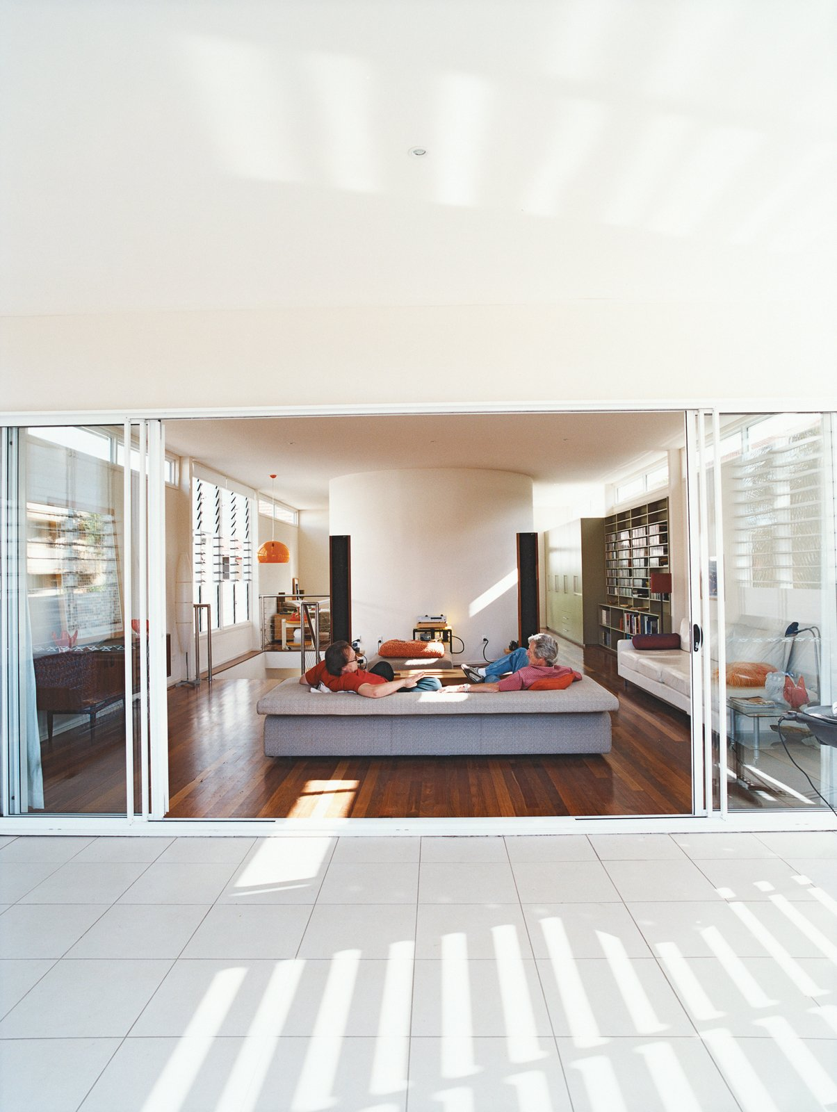 Clayden and Sam Cutler, both former tour managers for rock bands, talk music in the spacious, uncluttered living room that opens onto the balcony. Tagged: Living Room, Medium Hardwood Floor, and Sofa.  Photo 4 of 8 in Minimalist Bachelor Pad in Brisbane