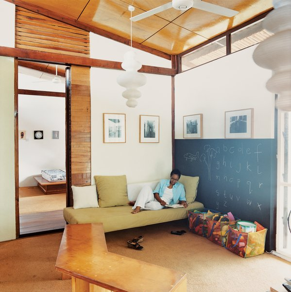 Sara Asafu-Adjaye rests on a couch in the TV room. The IKEA light fixture and other imports give the house its blend of Western and African, mass-produced and handmade.