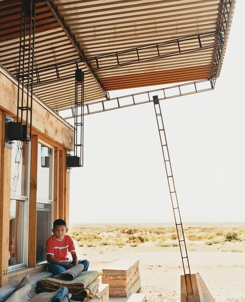Nicholas sits in the shade of the roof; students cut and hand-welded thousands of reclaimed rebar pieces into a complex grid that would support four bi-level <br><br>corrugated-steel roof panels.