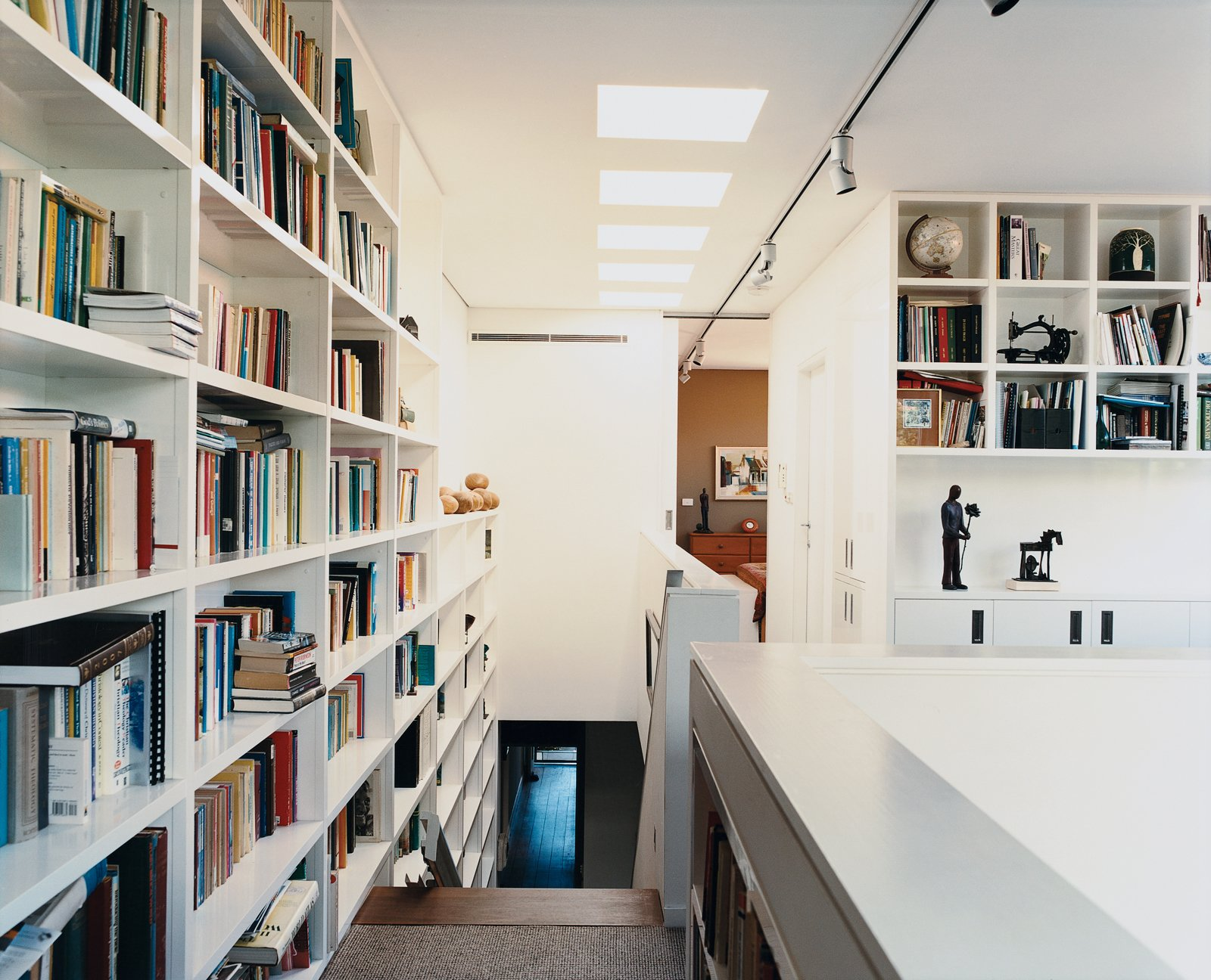 A wall of books travels the height of the stairs leading to Ann Wansbrough's office, which rests comfortably on the top floor despite her limited mobility. Tagged: Storage Room and Shelves Storage Type.  13+ Clever Bookcase Solutions by Erika Heet from The First Wave